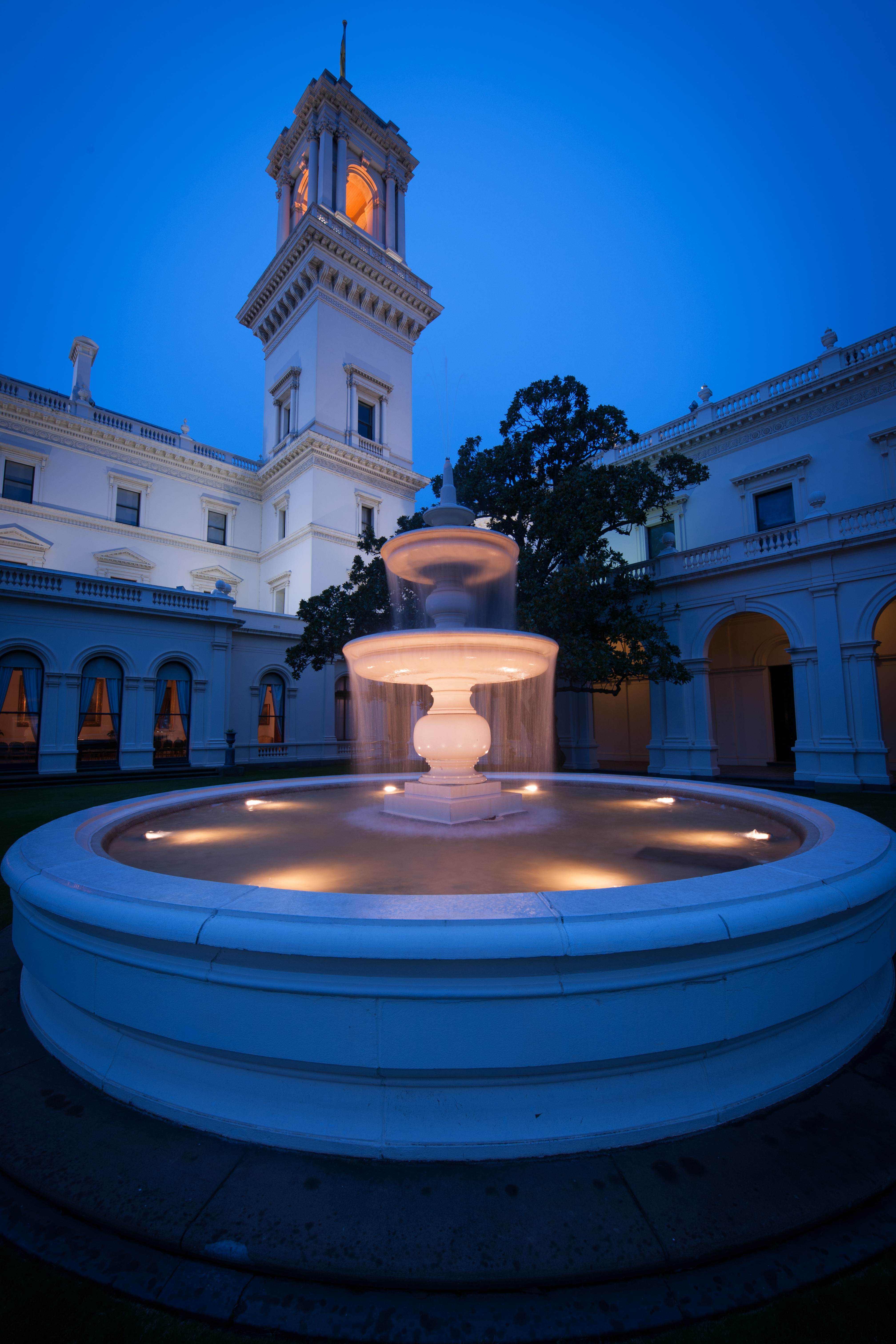 fountain at government house lit up at dusk.