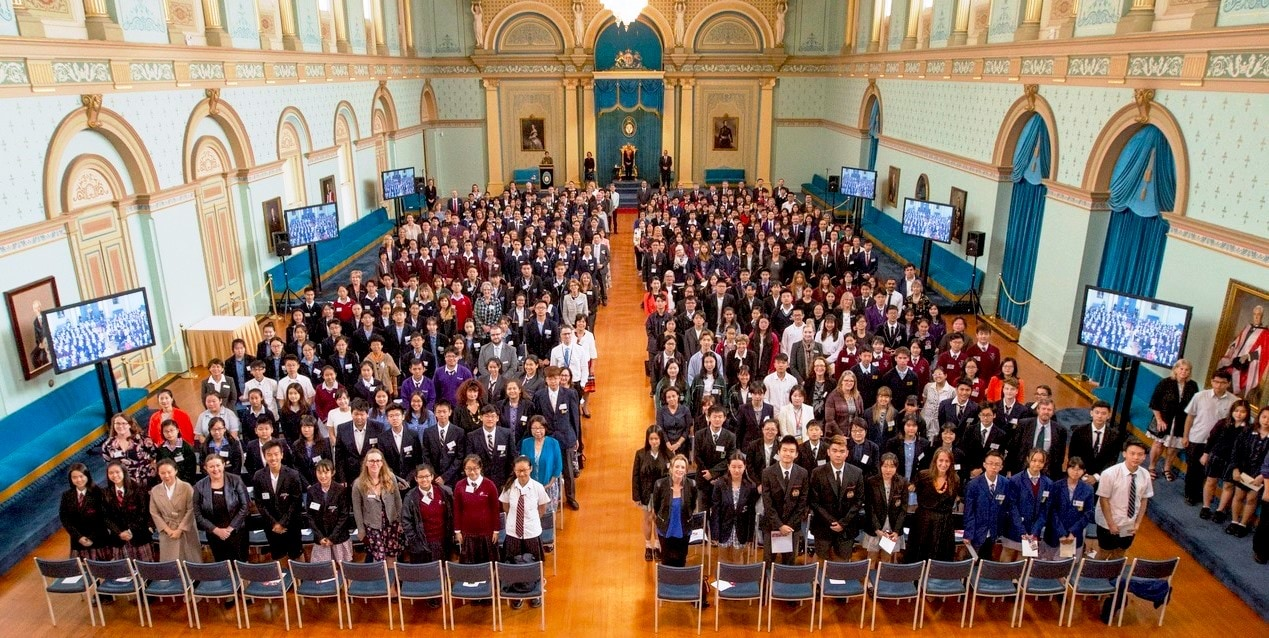 Hundreds of international students in a group photograph in the ballroom.