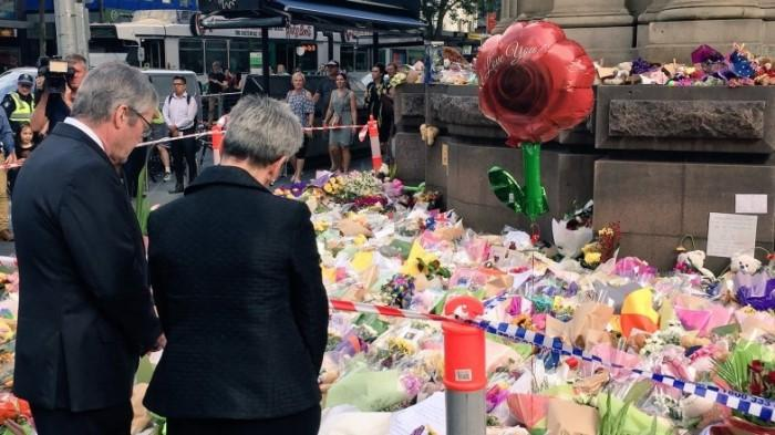 Her Excellency the Hon Linda Dessau AC and Mr Anthony Howard laying flowers at the Bourke Street tribute