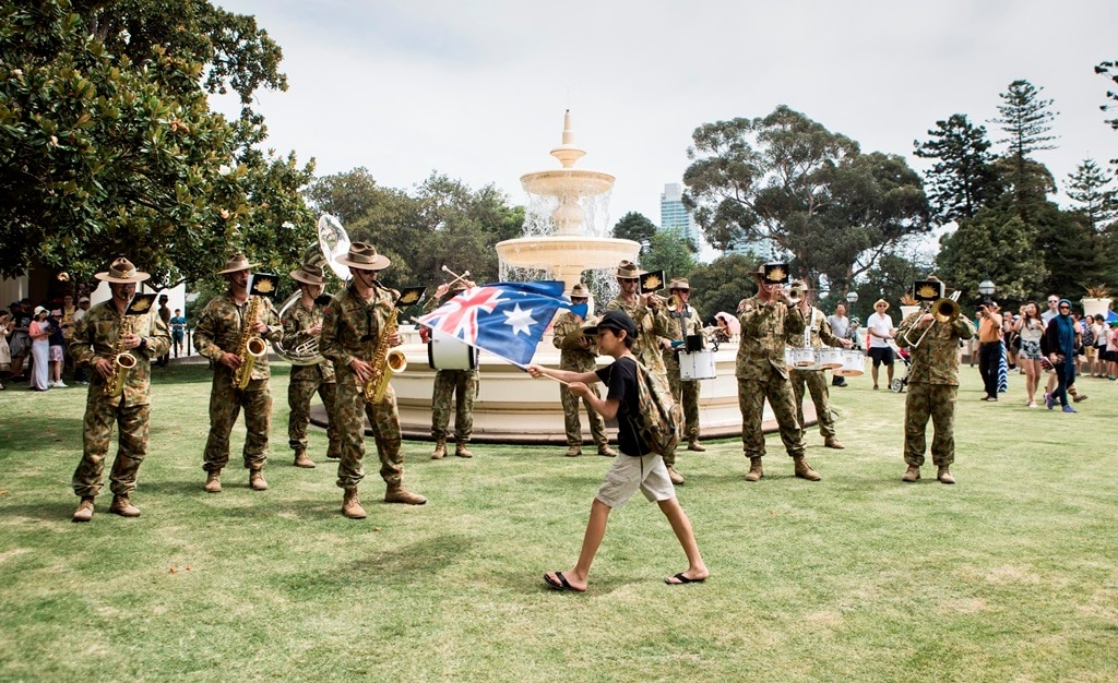 Army band playing in Fountain Court with boy waving Australian flag